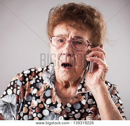 Surprised seniors talking mobile phone. Old adult mature woman. Shock