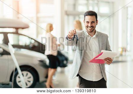 Elegant handsome salesperson working at car dealership