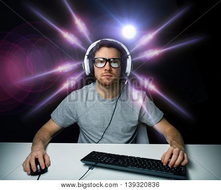 technology, gaming, entertainment, let's play and people concept - young man in headset and eyeglasses with pc computer playing game and streaming playthrough or walkthrough video over light