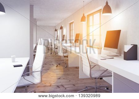 Coworking office interior with wooden floor white desks blank computer monitors and window with city view and sunlilght. Toned image 3D Rendering