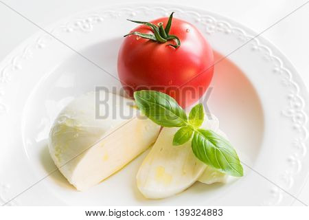 Close up of mozzarella cheese with tomato fresh basil and olive oil as ingredients for caprese salad on white plate.