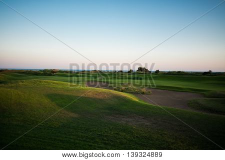 Beautiful golf course with sand trap and sea in the background at sunset