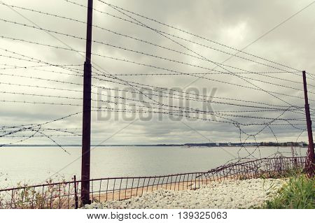 imprisonment, restriction concept - barb wire fence over gray sky and sea