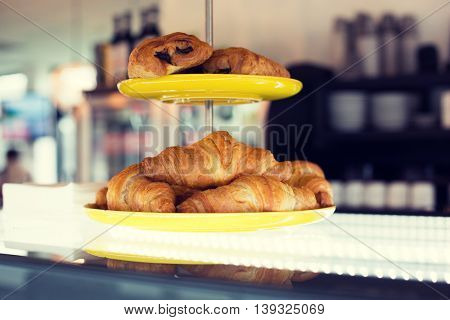 food, baking, junk-food and unhealthy eating concept - close up of croissants and buns on cake stand at cafe or bakery