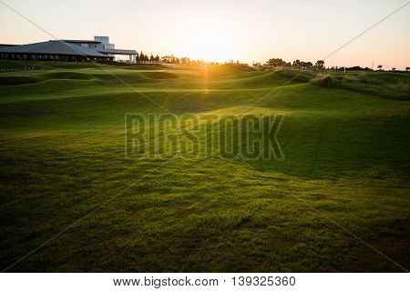 Beautiful golf club house with rays of sun at sunset