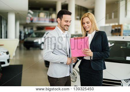 Elegant young salesperson working at car dealership