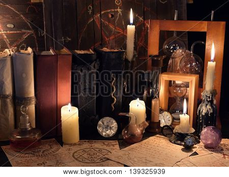 Witch table with magic objects, burning candles and old mystic parchments. Halloween concept, scary ritual or spell with occult and esoteric symbols