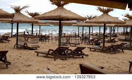 Sunbeds and thatched umbrellas on the beach. yellow sand and waves