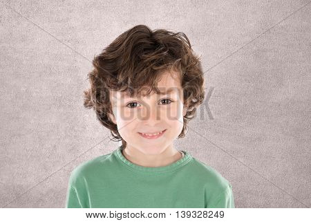 Smiling boy with six years old looking at camera on a grey background