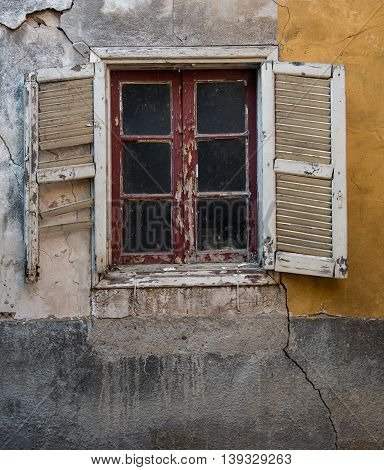 Closed broken window on a colorful wall. Concept of abandonment and desolation.