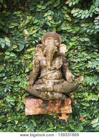 The hindu god Ganesha in front of a green wall.