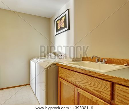 Bright Laundry Room With Wood Cabinets