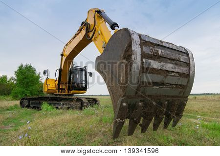 Big yellow excavator in green field at summer day, closeup of excavator bucket