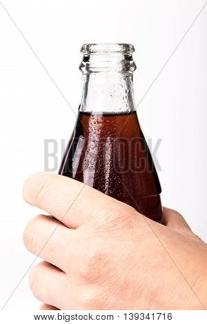 Hand Holding A Red Soda Coke Bottle.