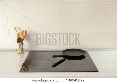 Cooking pan wooden spoons in modern kitchen with induction stove