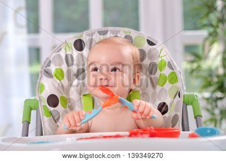 Baby Holding Itself With A Spoon And Fork