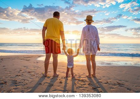 Grandfather and grandmother with grandson holding hands of each other on the beach at susnet