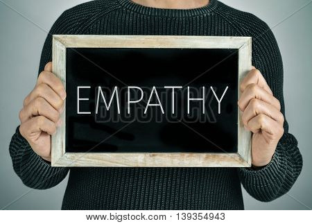 closeup of a young caucasian man showing a chalkboard with the text empathy written in it