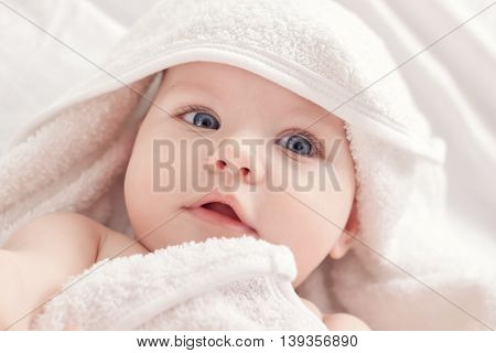 Baby after bath under white towel, close up