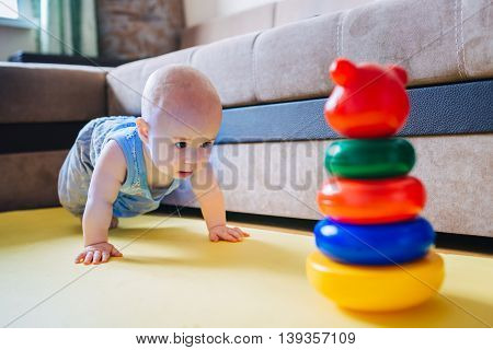 Cute little kid trying to get to the toy.