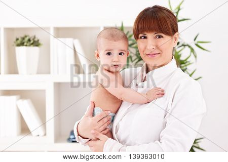 Baby and doctor pediatrician in office, close up