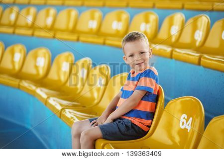 Little Boy Sitting In An Empty Stadium Among Yellow Plastic Numbered Seats And Applauds.