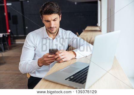 Handsome young concentrated attractive man using cellphone while working with laptop in the office