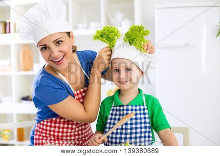 Smiling Beautiful Mother And Child With Chef's Hat Prepare Lettuce