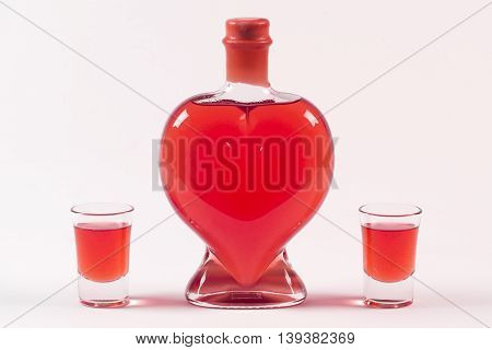 Bottle of alcohol with heart shape and two glasses for brandy or any strong alcohol. Red beverage.