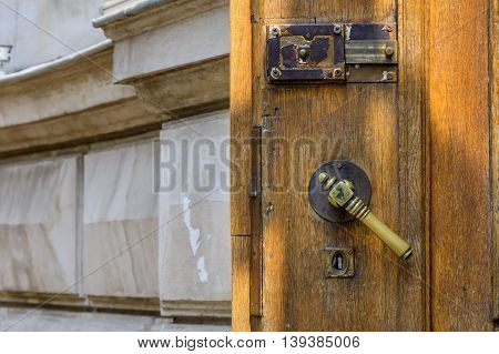 Horizontal View With Opened Old Door Closeup. Old Doorknob At Wood Front Door And Gray Wall..