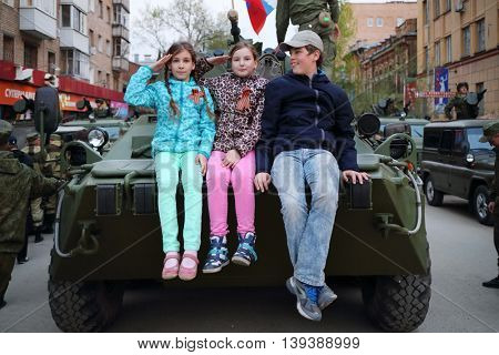 SAMARA - MAY, 6, 2015: Boy and two girls (with model releases) sitting on armored vehicle in Samara during military celebration. Red Square is not affected by military equipment on parade May 9th