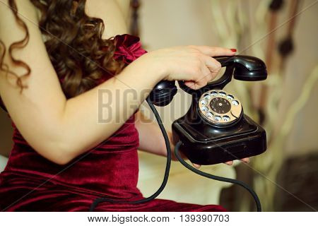 Hands of woman in red dress hold retro telephone in studio, close up