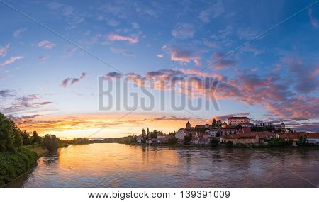 Castle rising on a hill at riverbank. Ptuj at sunset.