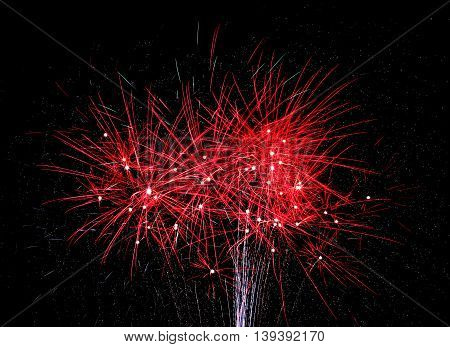 Bright red fireworks explode in the nightime sky