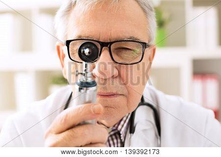 Otolaryngologist specialist looking through otoscope, healthcare concept