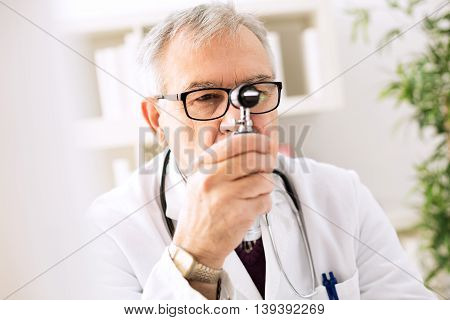 Otolaryngologist specialist looking through otoscope, close up poster
