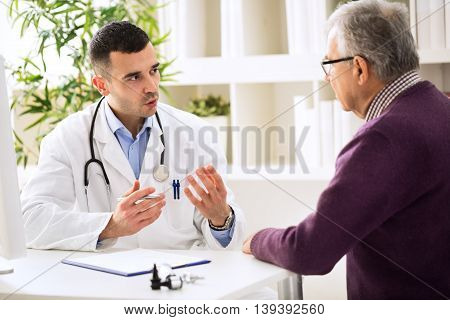 Young doctor talking with old patient in clinic