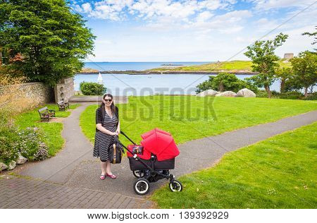 Young mother on a sunny day out in the park with her twin babies in the pushchair