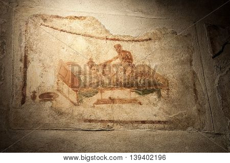 POMPEII, ITALY, MAY 10, 2012:  Erotic Fresco from the largest Pompeii brothel, on the wall of the ancient ruined city