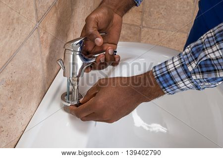 Close-up Of Male Plumber's Hand Fixing Tap Of Sink