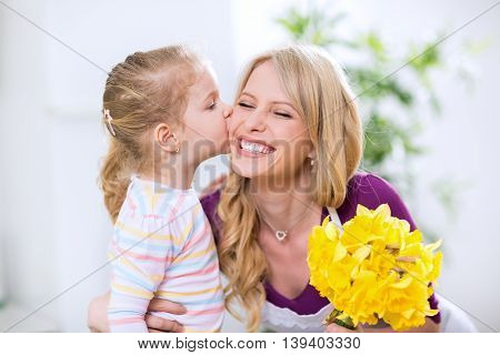 Daughter Giving Flowers And Kiss To Smiling Happy Mohter