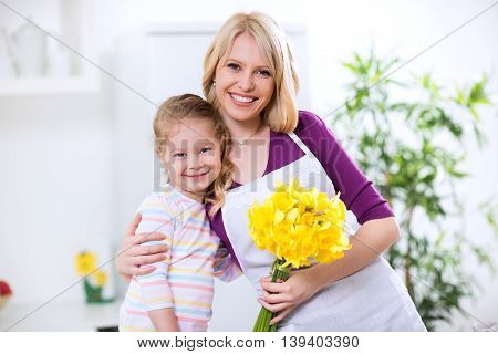 Child and mother in the embrace with flowers for mothers day
