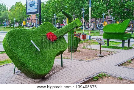 YEREVAN ARMENIA - MAY 29 2016: The park next to the Opera Theater decorated with installation of musical instruments - piano saxophone and guitar covered with growing grass on May 29 in Yerevan.