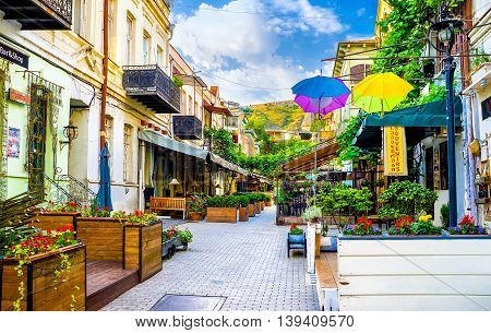 TBILISI GEORGIA - MAY 28 2016: The beautiful tourist street full of cafes and restaurants with outdoor patios decorated with flowers interesting sign boards and colorful umbrellas on May 28 in Tbilisi.