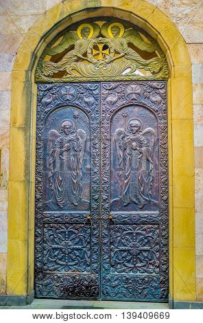TBILISI GEORGIA - MAY 28 2016: The entrance to Anchiskhati Basilica of St Mary decorated with icons and traceries stamped on metal on May 28 in Tbilisi.