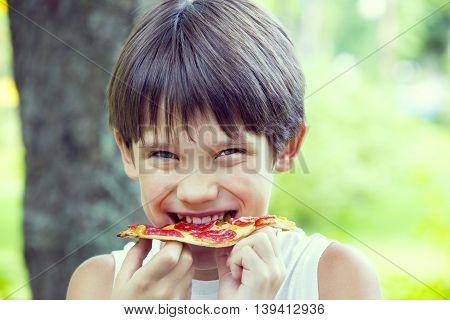 boy eating pizza on the nature Children
