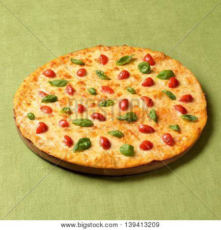 Pizza Margharita on green linen background. Popular fast food around the World.