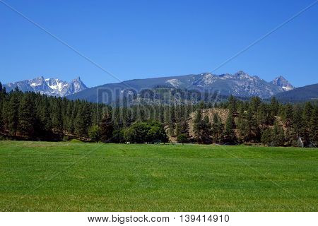 The Bitterroot Mountains provide a beautiful background for forest and ranch fields in Montana.