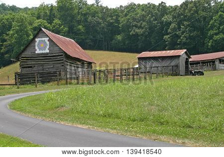 a curving driveway approaches farm buildings, the barn has a quilt square attached