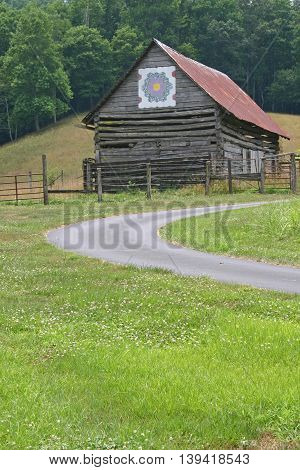 a curving driveway in front of an old barn with a quilt square